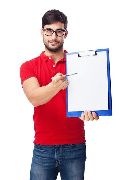 Adolescente feliz sujetando un bolígrafo y un sujetapapeles Foto gratis