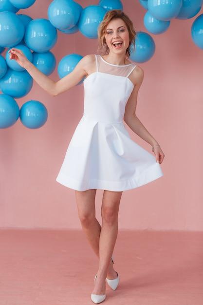 Adolescente feliz en el vestido blanco que baila solamente en su fiesta de cumpleaños. Foto gratis