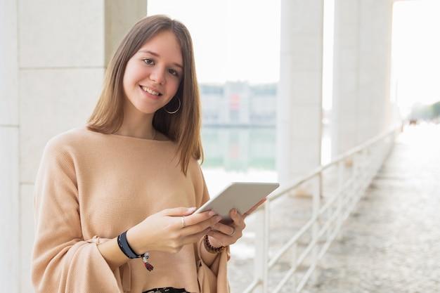 Adolescente femenino feliz que hojea en la tableta al aire libre Foto gratis