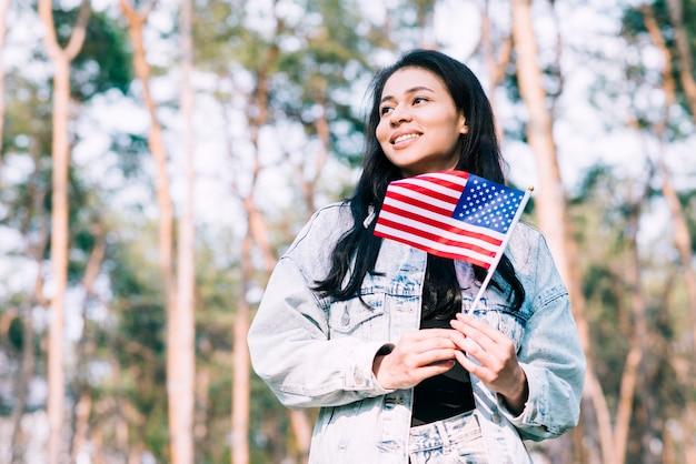 Adolescente hispana, tenencia, bandera estadounidense, en, palo Foto gratis