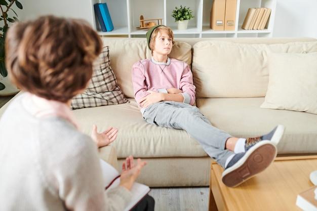 Adolescente indiferente ignorando la pregunta del psicólogo Foto Premium