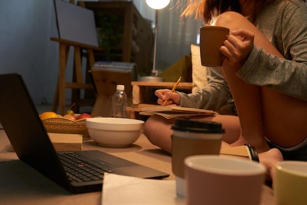 Adolescente irreconocible sentado en la computadora portátil tomando notas y bebiendo té Foto gratis