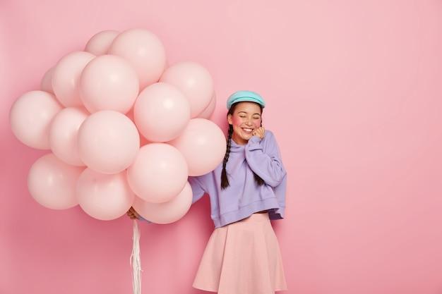 Una adolescente llena de alegría mantiene los ojos cerrados, sonríe ampliamente, muestra los dientes blancos, usa boina, sudadera y falda, sostiene globos inflados, celebra la licenciatura, aislado en la pared rosada Foto gratis