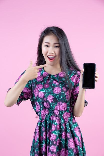 Adolescente mostrando teléfono y emociones faciales. Foto gratis