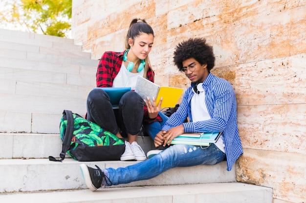Adolescente multi étnica pareja sentada en la escalera estudiando juntos Foto gratis