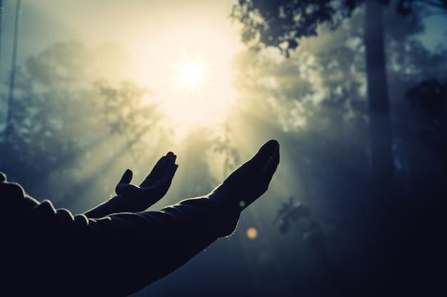 Adolescente con la oración en la naturaleza soleada. Foto gratis