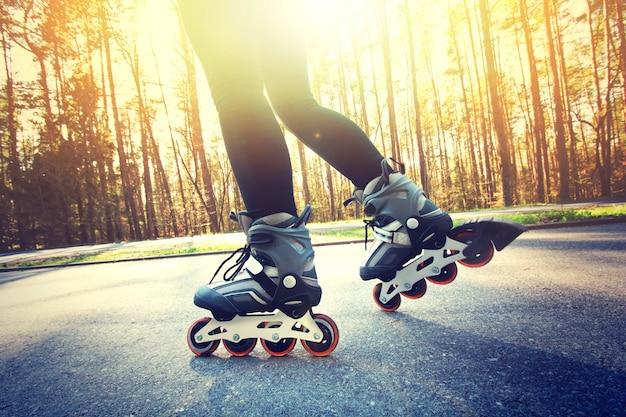 Adolescente en patines de ruedas en el verano. Foto gratis