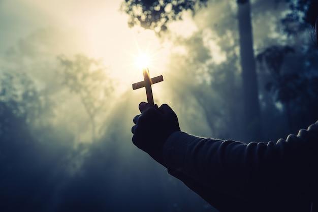 Adolescente que ruega con la cruz en naturaleza soleada. Foto gratis