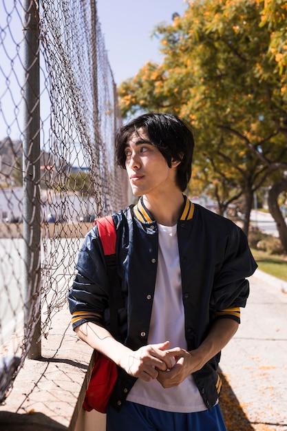 Adolescente serio mirando a otro lado a través de la cerca en la calle Foto gratis