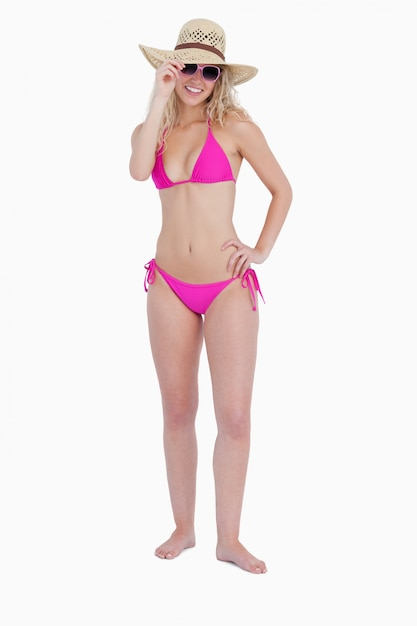 Adolescente sonriente vistiendo un traje de baño rosa mientras ...