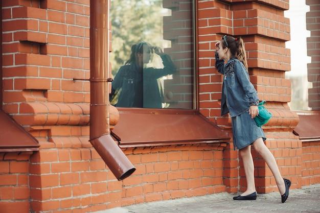 Adolescente en vestido de mezclilla azul mira en la ventana del edificio de ladrillo rojo al aire libre Foto Premium