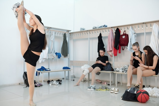 Las adolescentes decididas con pompón practicando split en el vestuario mientras sus compañeros de grupo descansando en un banco Foto Premium
