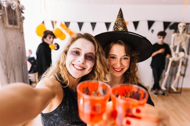 Adolescentes en disfraces de halloween en la fiesta haciendo selfie Foto gratis