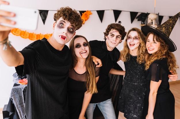 Adolescentes en disfraces de halloween haciendo selfie Foto gratis
