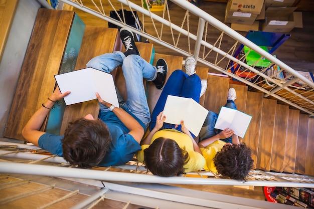 Adolescentes irreconocibles que leen en la escalera Foto gratis