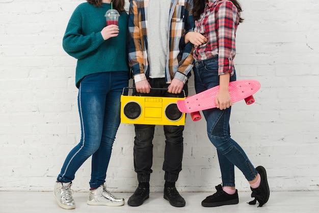 Adolescentes con monopatín y radio Foto gratis