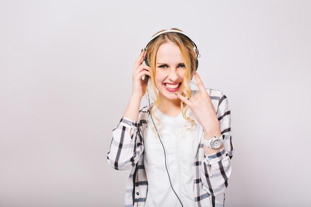 Adorable chica rubia vestida con jersey blanco sonríe desafiante, escucha música rock y se divierte. mujer joven con estilo en auriculares con reloj de pulsera de moda muestra signo de heavy metal y baile. Foto gratis