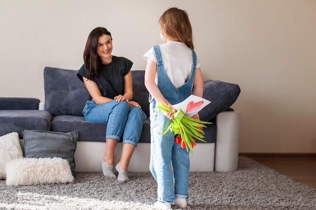 Adorable jovencita sorprendente madre con regalos Foto gratis