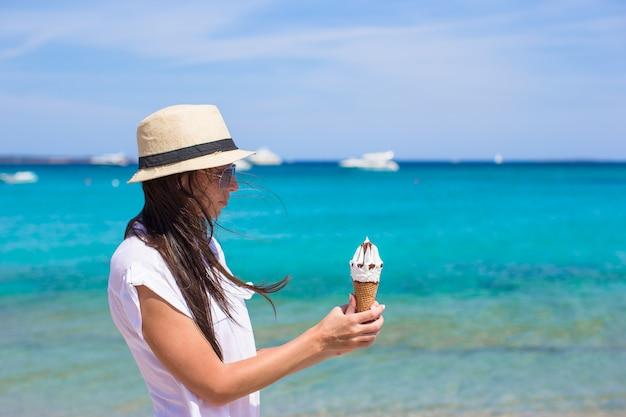 Adorable mujer comiendo helado en playa tropical Foto Premium