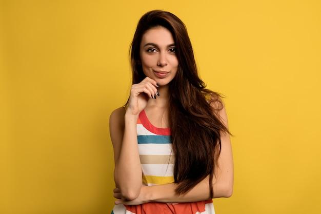 Adorable mujer encantadora con cabello largo castaño con vestido brillante de verano posando con una sonrisa adorable. Foto gratis
