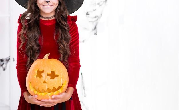 Adorable niña con calabaza tallada para halloween Foto gratis