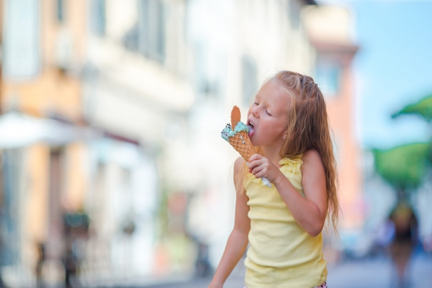 Adorable niña comiendo helado al aire libre en verano en la ciudad Foto Premium