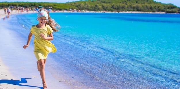 Adorable niña divertirse en la playa tropical durante las vacaciones Foto Premium