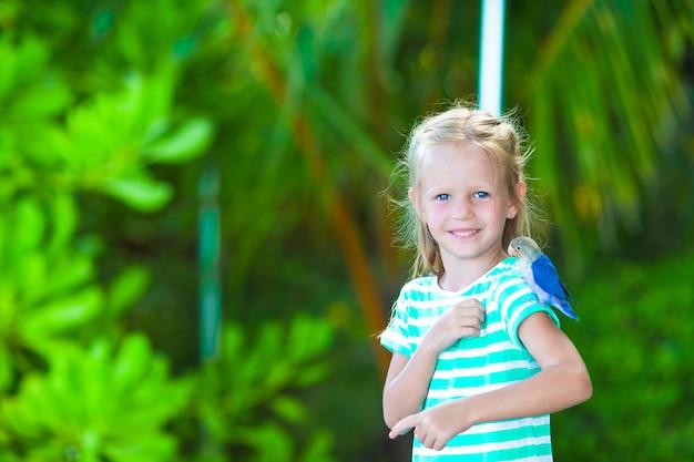 Adorable niña feliz en la playa con pajarito colorido Foto Premium