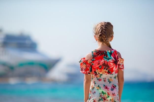 Adorable niña en el fondo de la playa big lainer en grecia Foto Premium