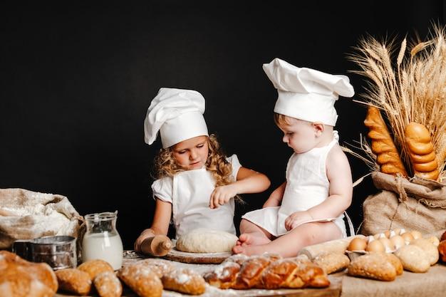 Adorable niña con niño en la mesa de cocina Foto Premium