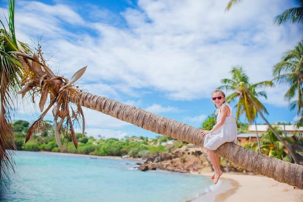Adorable niña sentada en la palmera durante las vacaciones de verano en la playa blanca Foto Premium