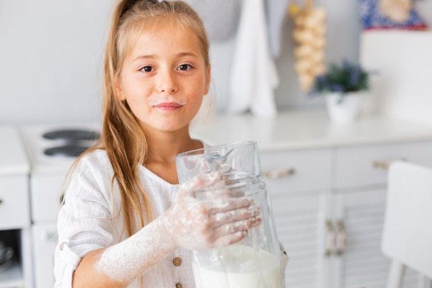 Adorable niña sosteniendo una taza de leche Foto gratis