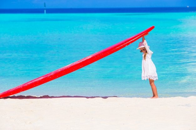 Adorable niña con tabla de surf roja grande en tropical playa blanca Foto Premium