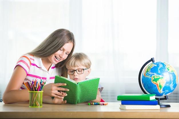 Adorable niño estudiando con su madre en casa. familia haciendo la tarea juntos. joven madre ayudando a su hijo a aprender una tarea. Foto Premium