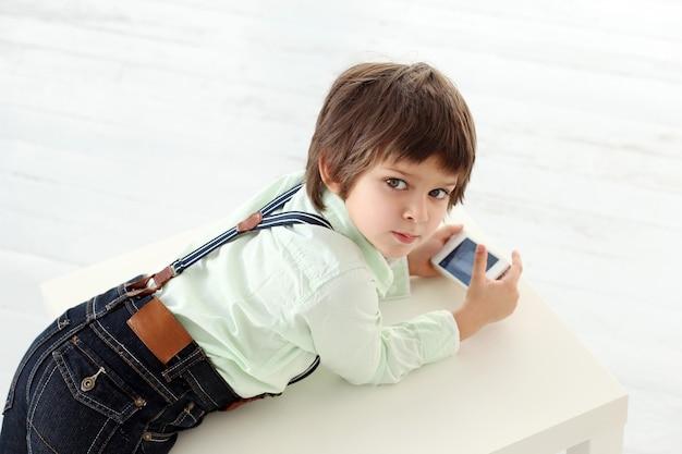 Adorable niño jugando con un teléfono inteligente Foto gratis