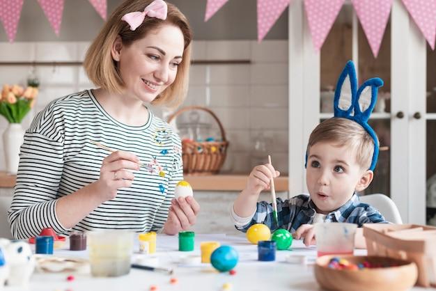 Adorable niño pintando huevos de pascua con madre Foto gratis