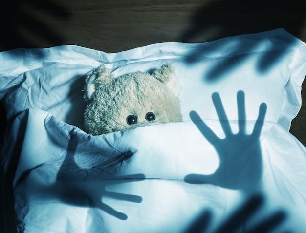 Adorable oso de peluche acostado en la cama, asustado Foto Premium