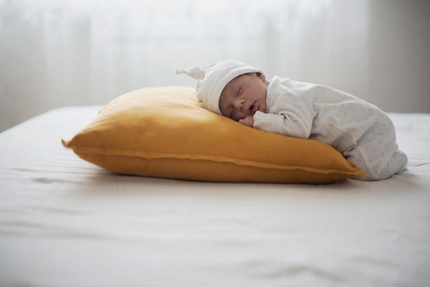 Adorable recién nacido durmiendo sobre una almohada amarilla Foto gratis