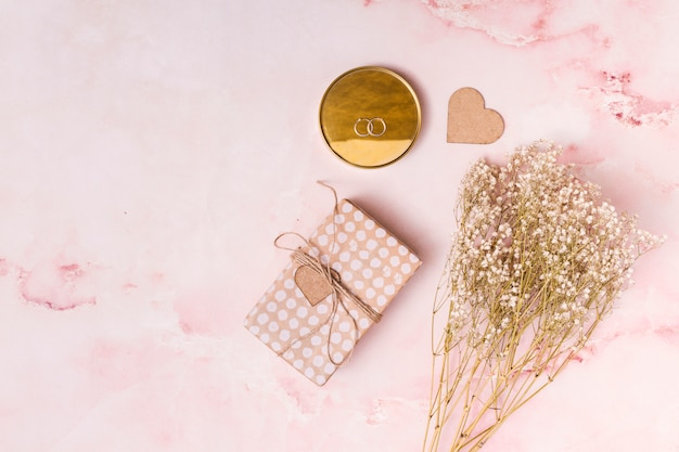 Adorne el corazón cerca del manojo de flores, presente cuadro y anillos en redondo Foto gratis