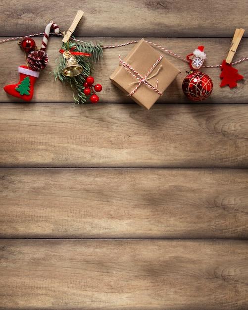 Adornos navideños colgando sobre fondo de madera Foto gratis