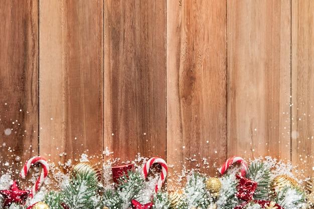 bf282718600 Adornos navideños con nieve sobre fondo de madera