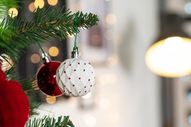 Adornos rojos y blancos colgando de un árbol de navidad de cerca Foto Premium