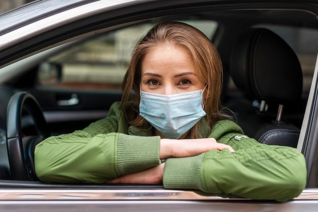 Adulto joven con una máscara de protección en el automóvil Foto Premium