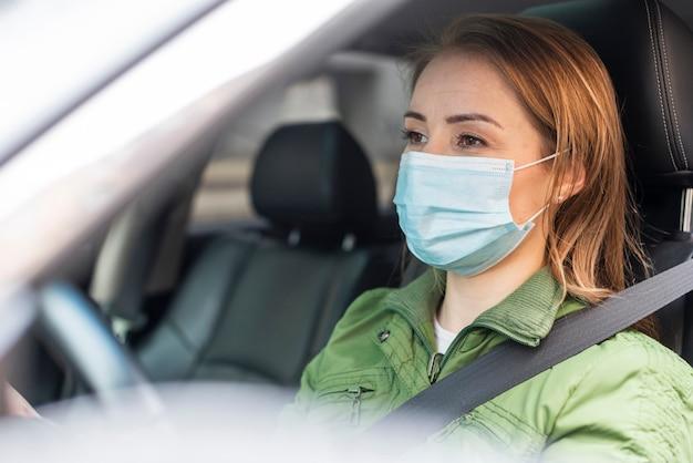 Adulto joven con una máscara de protección y conducir Foto Premium