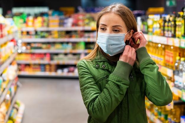Adulto joven con una máscara de protección en una tienda Foto gratis