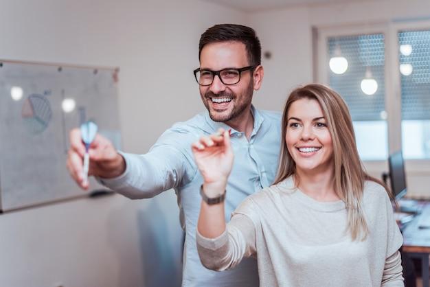 Adultos jovenes hermosos que juegan dardos en casa. Foto Premium