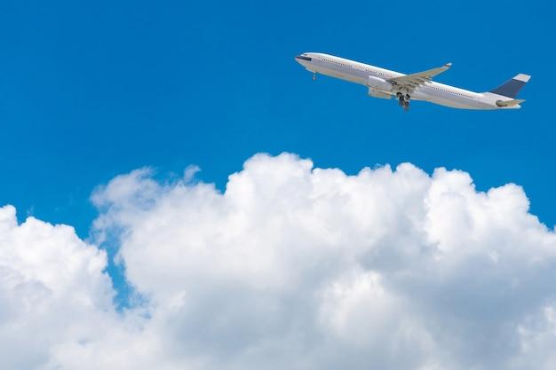 Aeroplano comercial que vuela sobre el cielo azul brillante y las nubes blancas. Foto Premium