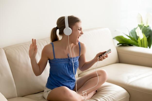 Aficionado a la música joven usando auriculares cantando Foto gratis