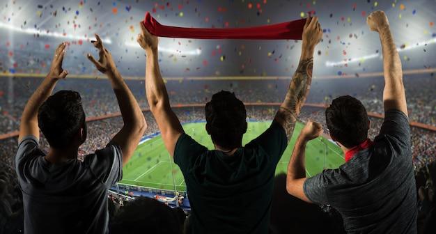 Aficionados en estadio con bufanda Foto gratis