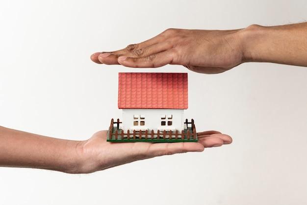 Agente de bienes raíces y cliente sosteniendo una casa de juguetes Foto gratis